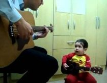 Baby boy playing Don't Let Me Down on the guitar with his dad.