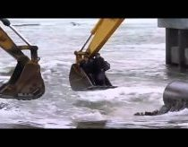 People crossing the river in Russia with excavators