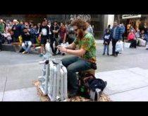 Gatvės muzikantas groja plastikiniais vamzdžiais