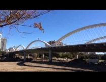 Man rides bike over West Seventh Street bridge arches