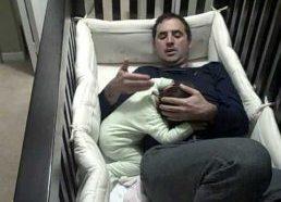 Tėtis įlipa į vaikišką lovelę kad nuramintų verkiantį kūdikį