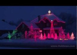 Kalėdinėm eglutėm papuoštas namas