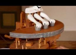 Medinis žaislas daro triukus su puodeliais ir komuoliuku
