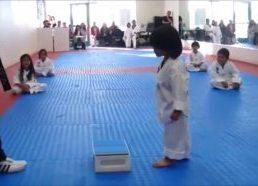 Mažas berniukas bando perskelti lentelę - taekwondo